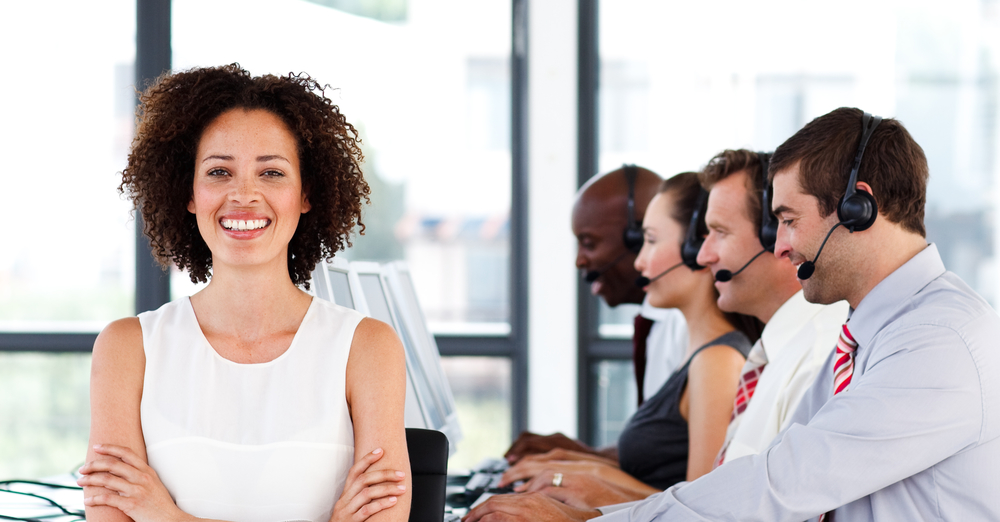 Happy female manager working in a call center with her colleagues